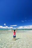 Flicka som spelar på stranden arkivfoton