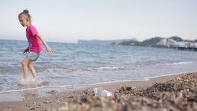 Flicka som spelar på stranden med kiselstenar arkivfilmer