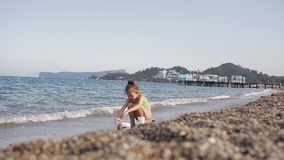 Flicka som spelar på stranden med kiselstenar stock video