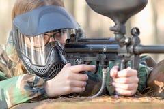 Flicka som spelar paintball i overaller med ett vapen Royaltyfri Foto