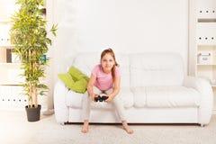 Flicka som spelar videogamen Royaltyfria Foton