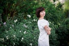 Flicka som står near lilor royaltyfri bild