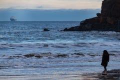 Flicka som stirrar på det grova havet och färjan, Tynemouth, UK royaltyfri fotografi