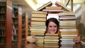 Flicka som stirrar till och med böcker stock video