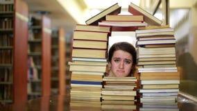 Flicka som stirrar till och med böcker lager videofilmer