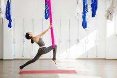 Flicka som sträcker ben med hjälp av hängmattan Flyg- övningsyoga Royaltyfria Bilder