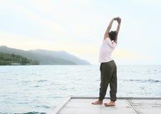 Flicka som sträcker på bryggan vid havet royaltyfri fotografi