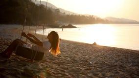 Flicka som svänger på ett hjul med solnedgång nära arkivfilmer
