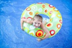 Flicka som svävar i simbassäng Royaltyfri Foto