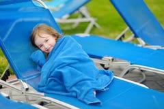 Flicka som täckas med en handduk som sitter nära pöl Arkivfoto