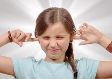 Flicka som täcker henne öron, för att säga stoppet som gör högt oväsen som ger mig Arkivfoto