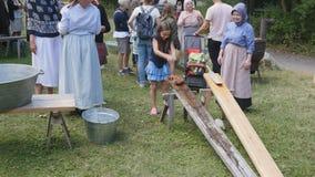 Flicka som tömmer linne i traditionell tvätteri i Skansen, Stockholm, Sverige arkivfilmer