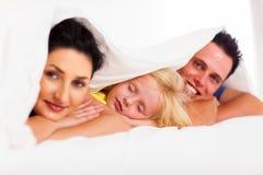 Flicka som ta sig en tupplur med föräldrar Arkivfoton
