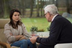 Flicka som talar med äldre psykiater Fotografering för Bildbyråer