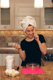 Flicka som talar på mobiltelefonen och ler, medan laga mat arkivfoto