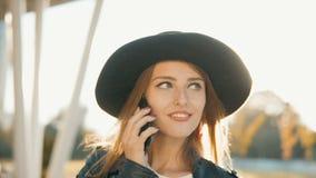 Flicka som talar på telefonen, medan gå stock video