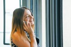Flicka som talar på telefonen nära fönstret arkivfoto