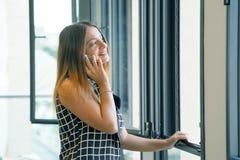 Flicka som talar på telefonen nära fönstret arkivbild