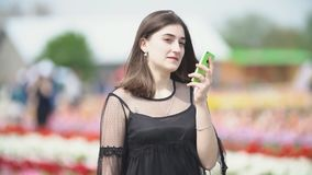 Flicka som talar p? telefonen p? tulpanf?ltet arkivfilmer