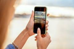 Flicka som tar bilder av ett landskap, närbild av en telefon i henne royaltyfria bilder
