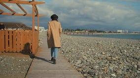 Flicka som tar en ensam promenad på en strand stock video