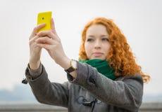 Flicka som tar en selfie. Arkivfoto