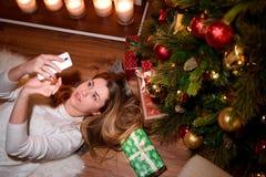 Flicka som tar en selfie för nytt år i ett dekorerat område arkivbilder
