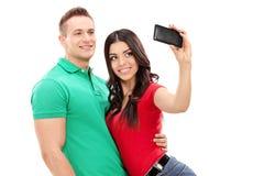 Flicka som tar en selfie med hennes pojkvän med en mobiltelefon Royaltyfri Bild