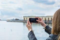 Flicka som tar fotoet med mobiltelefonen Arkivbilder