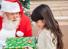 Flicka som tar julgåvan från Santa Claus Arkivfoton