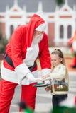 Flicka som tar kakor från Santa Claus Arkivbilder