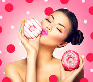 Flicka som tar sötsaker och färgrika donuts Fotografering för Bildbyråer