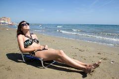 Flicka som tar solen på stranden royaltyfria bilder