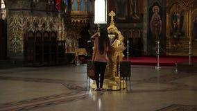 Flicka som tillber i ortodox kyrka stock video
