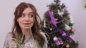 Flicka som tröttas för att dekorera julgranen, girland i munnen lager videofilmer