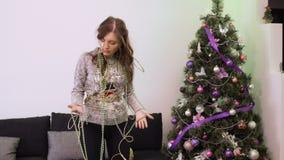 Flicka som tröttas för att dekorera julgranen för helgdagsaftonen för nytt år som är intrasslad i girland stock video