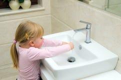 Flicka som tvättar henne händer arkivfoton