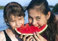 Flicka som två äter en skiva av vattenmelon Royaltyfri Fotografi