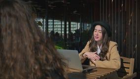 Flicka som två sitter på kaféterrass och talar i vår stock video