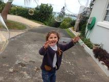 Flicka som tycker om att poppa för bubbla arkivbild