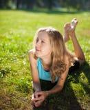 Flicka som tycker om avkoppling som ligger i det gröna gräset royaltyfri foto