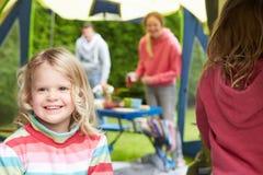 Flicka som tycker om campa ferie för familj på campingplats royaltyfria bilder