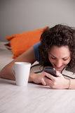 Flicka som tycker om hennes mobil, medan dricka från en råna Arkivbilder