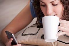 Flicka som tycker om hennes mobil, medan dricka från en råna Royaltyfri Fotografi