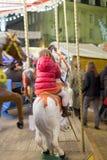 Flicka som tycker om karusellritt i ett nöjesfält, Royaltyfria Bilder