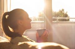 Flicka som tycker om morgonkaffe i vardagsrum fotografering för bildbyråer