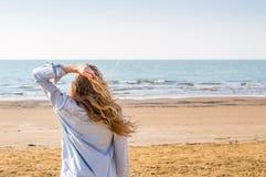 Flicka som tycker om solen på stranden Royaltyfria Bilder