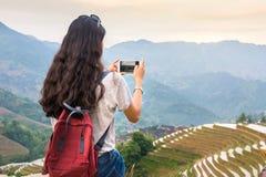 Flicka som tycker om solnedgång på den terrasserade risfältet i Longji, Kina Arkivbild