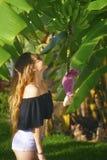 Flicka som undersöker naturen - undersökande bananträd, blomma och växa för frukter på ett grönt träd En le ung kvinna med gräspl Arkivfoto