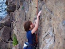 Flicka som upp klättrar en klippa royaltyfri fotografi